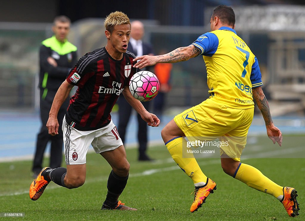 Keisuke Honda of AC Milan is challenged by Simone Pepe of AC Chievo Verona during the Serie A match between AC Chievo Verona and AC Milan at Stadio Marc'Antonio Bentegodi on March 13, 2016 in Verona, Italy.