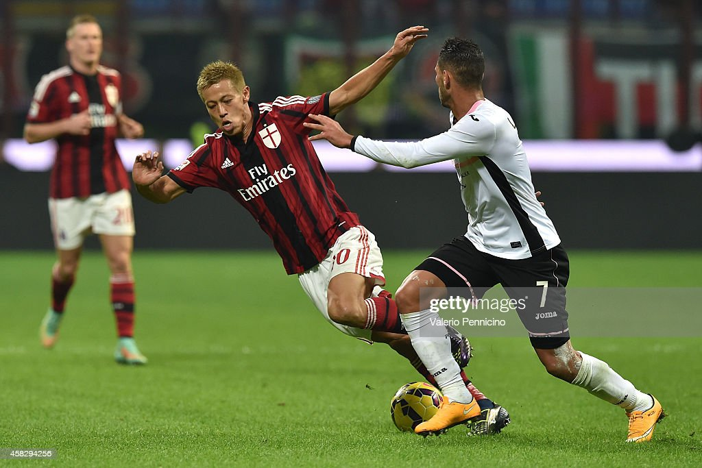 Keisuke Honda (L) of AC Milan is tackled by Achraf Lazaar of US Citta di Palermo during the Serie A match between AC Milan and US Citta di Palermo at Stadio Giuseppe Meazza on November 2, 2014 in Milan, Italy.