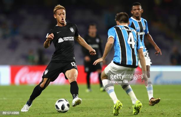 Keisuke Honda of CF Pachuca runs with the ball under pressure from Walter Kannemann of Gremio during the FIFA Club World Cup UAE 2017 semifinal match...