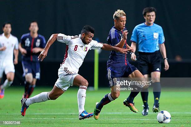 Keisuke Honda of Japan and Agnel Flores of Venezuela compete for the ball during the international friendly match between Japan and Venezuela at...