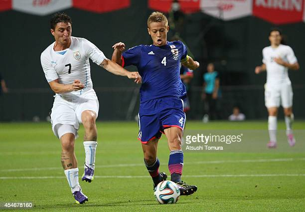 Keisuke Honda of Japan and Cristian Rodriguez of Uruguay compete for the ball during the KIRIN CHALLENGE CUP 2014 international friendly match...
