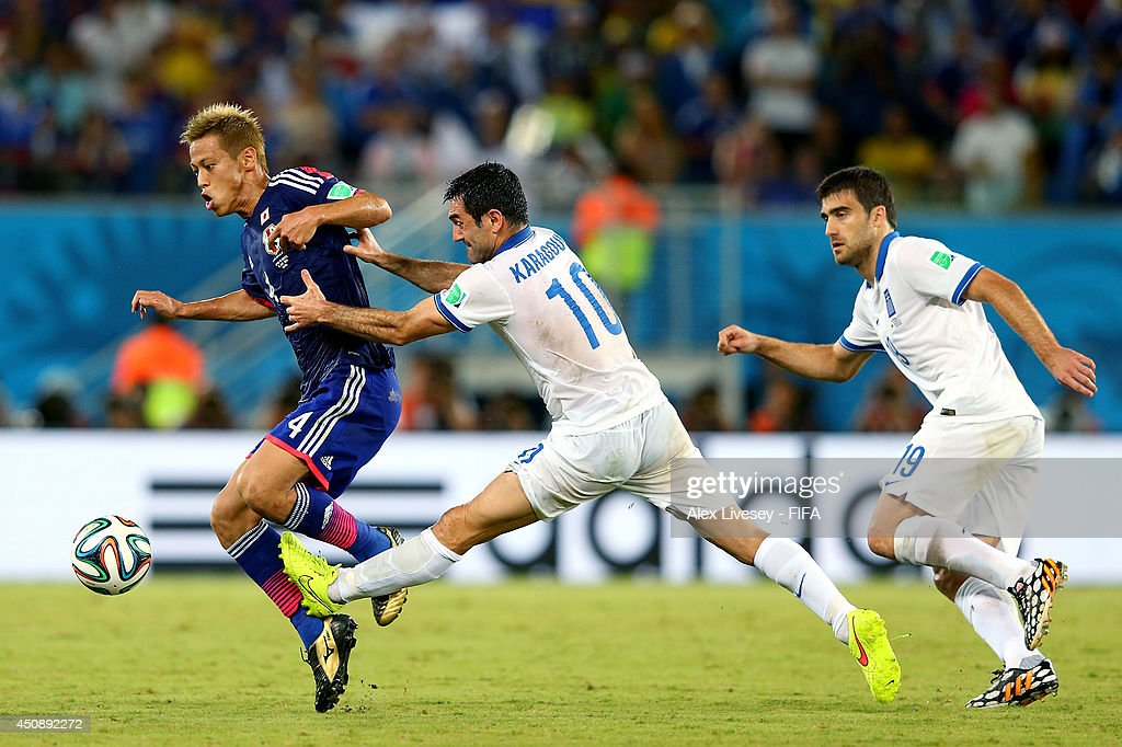Keisuke Honda of Japan and Giorgos Karagounis of Greece compete for the ball during the 2014 FIFA World Cup Brazil Group C match between Japan and Greece at Estadio das Dunas on June 19, 2014 in Natal, Brazil.