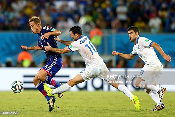Keisuke Honda of Japan and Giorgos Karagounis of Greece compete for the ball during the 2014 FIFA World Cup Brazil Group C match between Japan and...