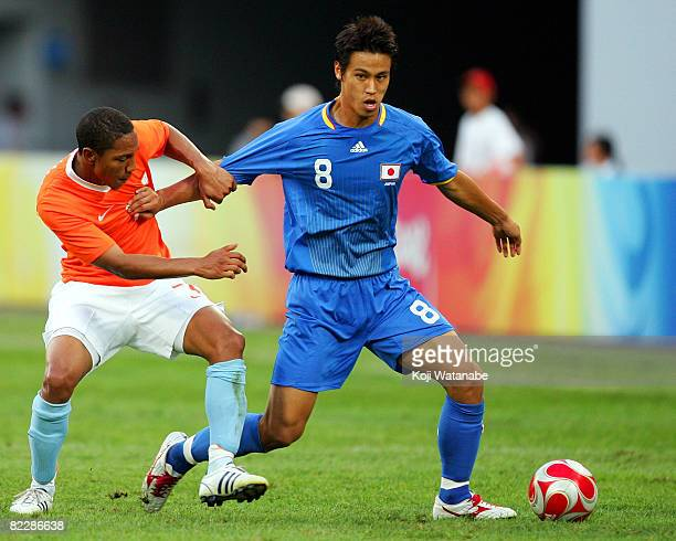 Keisuke Honda of Japan and Jonathan De Guzman of the Netherlands compete for the ball during the Men's Group B match between Netherlands and Japan at...