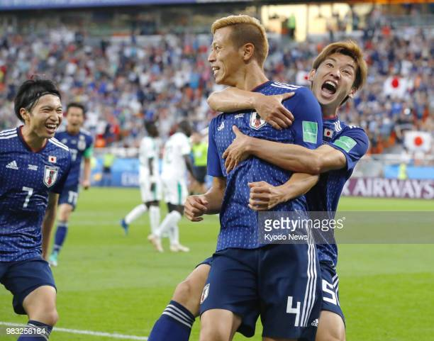 Keisuke Honda of Japan celebrates his equalizer with teammates Gaku Shibasaki and Yuya Osako during the second half of a World Cup Group H match...