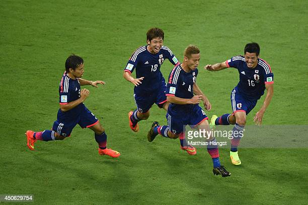 Keisuke Honda of Japan celebrates scoring his team's first goal with Yuto Nagatomo , Yuya Osako and Hotaru Yamaguchi during the 2014 FIFA World Cup...