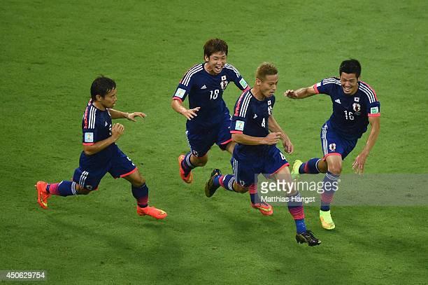 Keisuke Honda of Japan celebrates scoring his team's first goal with Yuto Nagatomo , Yuya Osako and Hotaru Yamaguchi during the 2014 FIFA World Cup...