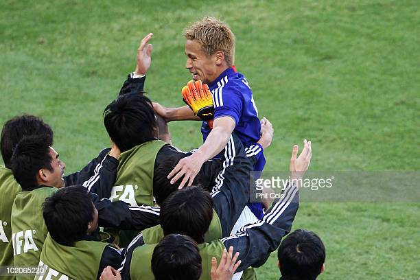 Keisuke Honda of Japan celebrates scoring the opening goal with team mates and coaching staff on the touchline during the 2010 FIFA World Cup South...