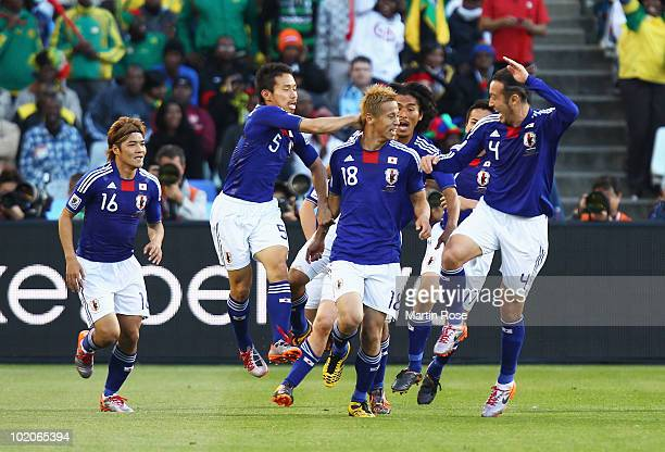 Keisuke Honda of Japan celebrates scoring the opening goal with team mates during the 2010 FIFA World Cup South Africa Group E match between Japan...