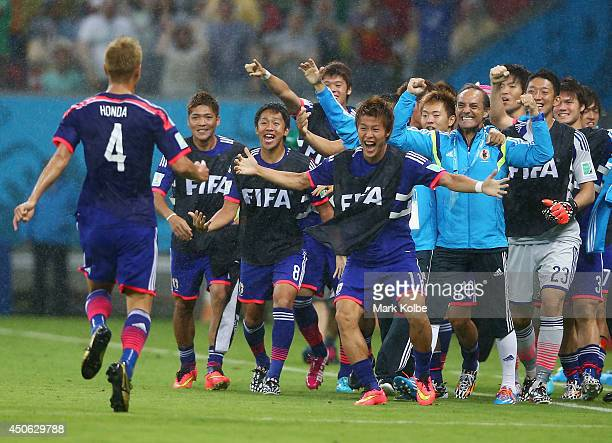 Keisuke Honda of Japan celebrates scoring the team's first goal on the sidelines during the 2014 FIFA World Cup Brazil Group C match between the...