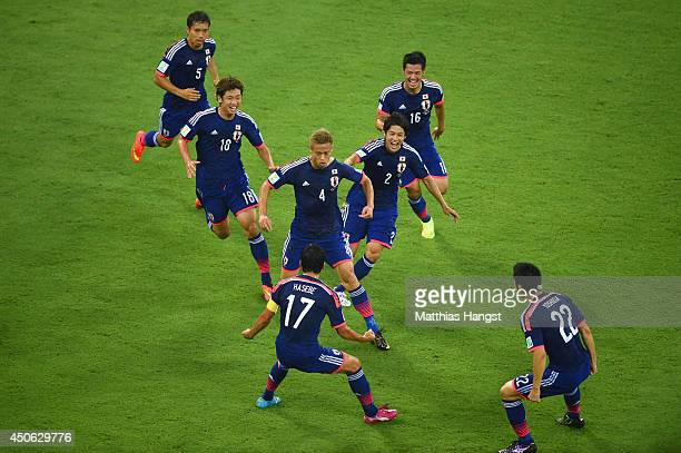 Keisuke Honda of Japan celebrates scoring the team's first goal with teammates during the 2014 FIFA World Cup Brazil Group C match between the Ivory...