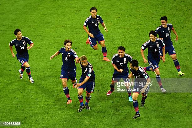 Keisuke Honda of Japan celebrates with team-mates after scoring the team's first goal during the 2014 FIFA World Cup Brazil Group C match between...