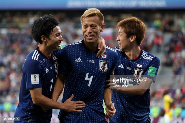 Keisuke Honda of Japan celebrates with teammates Yuya Osako and Gaku Shibasaki after scoring his team's second goal during the 2018 FIFA World Cup...