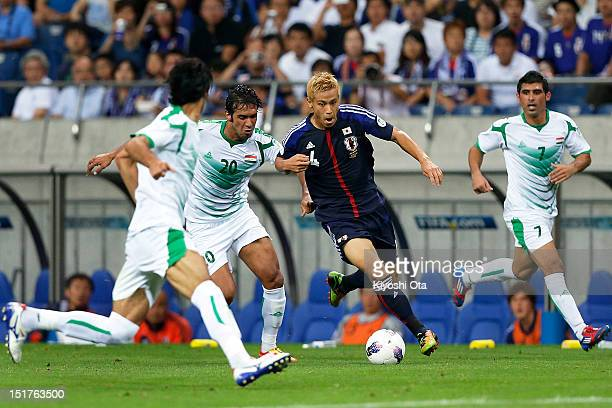 Keisuke Honda of Japan competes for the ball against Muthana Khalid of Iraq during the FIFA World Cup final qualifier match between Japan and Iraq at...