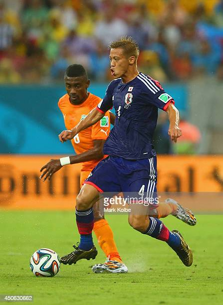 Keisuke Honda of Japan controls the ball against Salomon Kalou of the Ivory Coast during the 2014 FIFA World Cup Brazil Group C match between the...