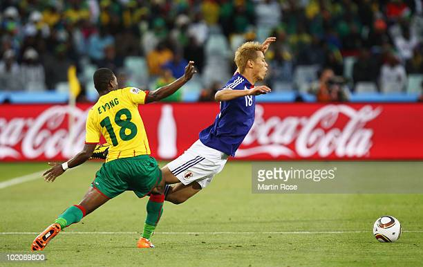 Keisuke Honda of Japan falls to the ground after being tackled by Enoh Eyong of Cameroon during the 2010 FIFA World Cup South Africa Group E match...