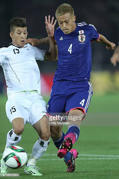 Keisuke Honda of Japan fends off Dhurgham Ismael of Iraq to kick a goal during the international friendly match between Japan and Iraq at Nissan...