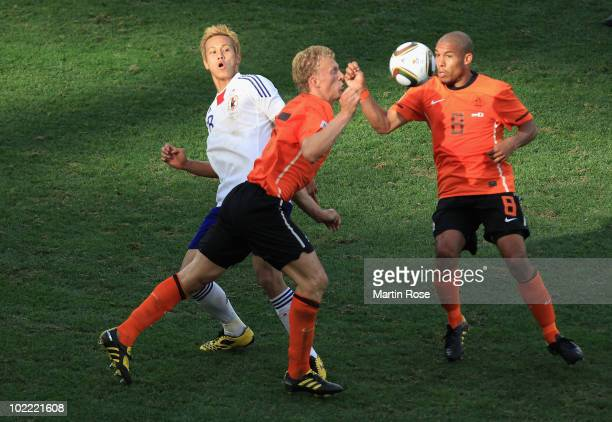 Keisuke Honda of Japan is tackled by Dirk Kuyt of the Netherlands as Nigel De Jong wins the ball during the 2010 FIFA World Cup South Africa Group E...