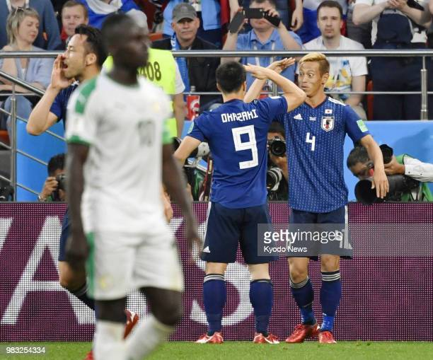 Keisuke Honda of Japan salutes teammate Shinji Okazaki after scoring an equalizer during the second half of a World Cup Group H match against Senegal...