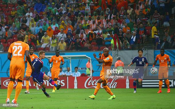 Keisuke Honda of Japan shoots and scores his team's first goal during the 2014 FIFA World Cup Brazil Group C match between the Ivory Coast and Japan...