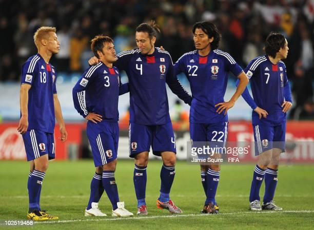 Keisuke Honda of Japan stands with Yuichi Komano of Japan as Komano is comforted by teammates Marcus Tulio Tanaka and Yuji Nakazawa after missing a...