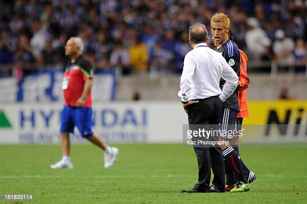 Keisuke Honda of Japan talks with head coach Alberto Zaccheroni after the FIFA World Cup final qualifier match between Japan and Iraq at Saitama...