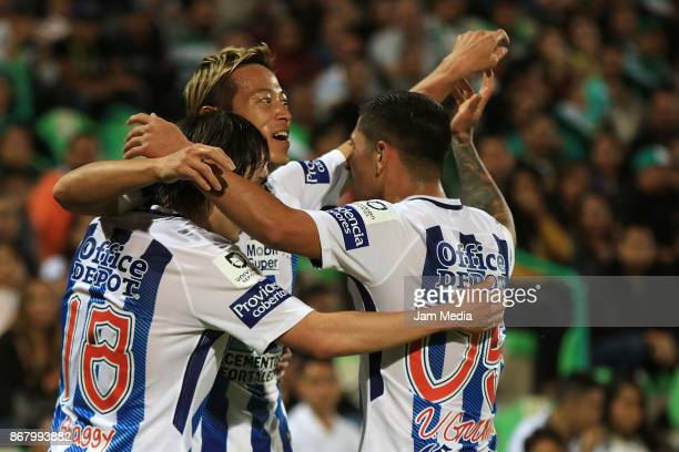 Keisuke Honda of Pachuca celebrates with teammates Victor Guzman and Jose Martinez after scoring the second goal of his team during the 15th round...