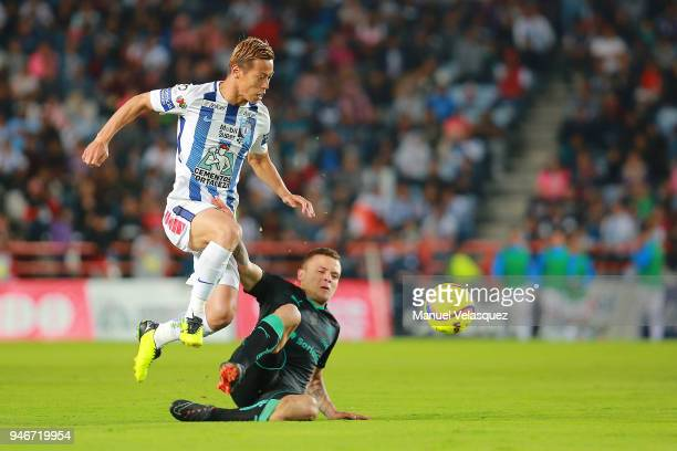 Keisuke Honda of Pachuca jumps with the ball over the slide of Jonathan Rodriguez of Santos during the 15th round match between Pachuca and Santos...