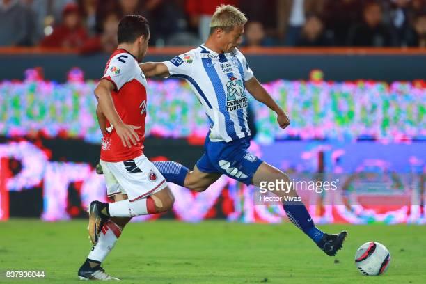 Keisuke Honda of Pachuca kicks the ball to score the fourth goal of his team against Jesus Paganoni of Veracruz during the sixth round match between...