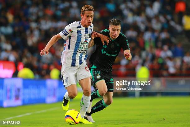 Keisuke Honda of Pachuca struggle for the ball against Jorge Flores of Santos during the 15th round match between Pachuca and Santos Laguna as part...