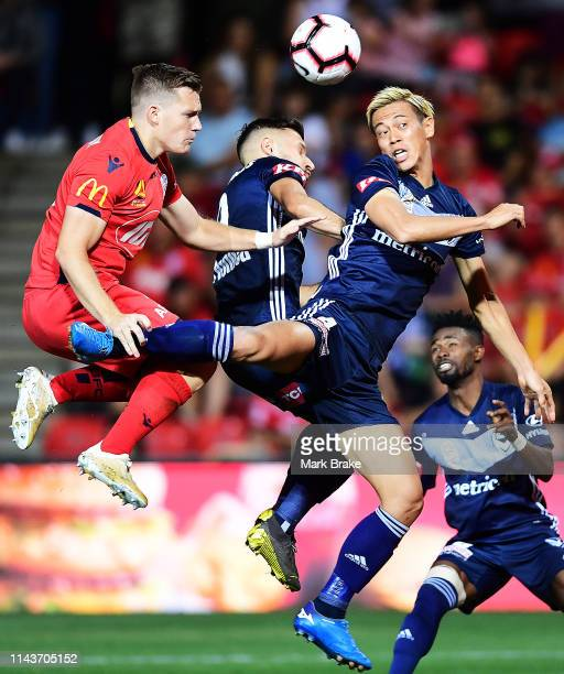 Keisuke Honda of the Victory attempts to head for goal in front of Scott Galloway of Adelaide United during the round 26 ALeague match between...