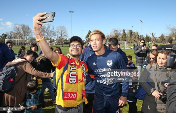 Keisuke Honda of the Victory poses for a photo with a supporter during a Melbourne Victory training session at Gosch's Paddock on August 17 2018 in...