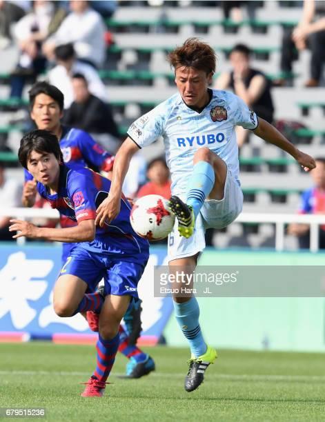 Keisuke Tanabe of FC Ryukyu controls the ball under pressure of Mao Kobayashi of FC Tokyo during the JLeague J3 match between FC Tokyo U23 and FC...