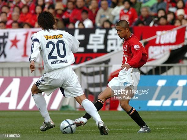 Keisuke Tsuboi of Urawa Red Diamonds and Akinori Nishizawa of Cerezo Osaka compete for the ball during the JLeague match between Urawa Red Diamonds...