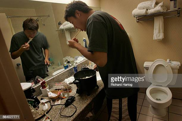 Keisuke Ueno of the Japan Samurai Bears checks the rice as he cooks it in his hotel room bathroom after a double–header vs Fullerton Flyers late...