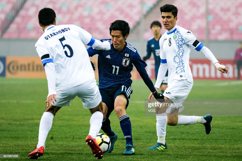 Keita Endo #11 of Japan and Abbosjon Otakhonov #5 of Uzbekistan compete for the ball during the AFC U-23 Championship quarter-final match between Japan and Uzbekistan at Jiangyin Stadium on January 19, 2018 in Jiangyin, Jiangsu Province of China.