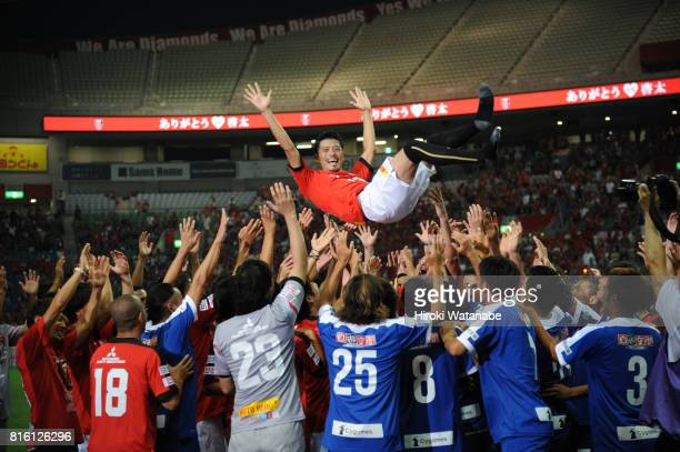 Keita Suzuki is tossed into the air by his former teammates after the Keita Suzuki testimonial match between Reds Legends and Blue Friends at Saitama...