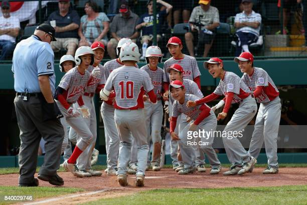 Keitaro Miyahara of Japan celebrates with teammates after hitting a solo home run against the Southwest Team from Texas in the fourth inning during...