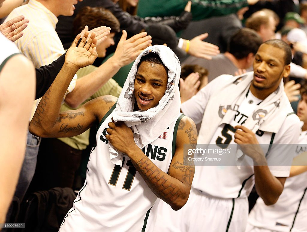 Keith Appling #11 and Adreian Payne #5 of the Michigan State Spartans celebrates a 84-61 win over the Purdue Boilermakers with fans at the Jack T. Breslin Student Events Center on January 5, 2013 in East Lansing, Michigan.