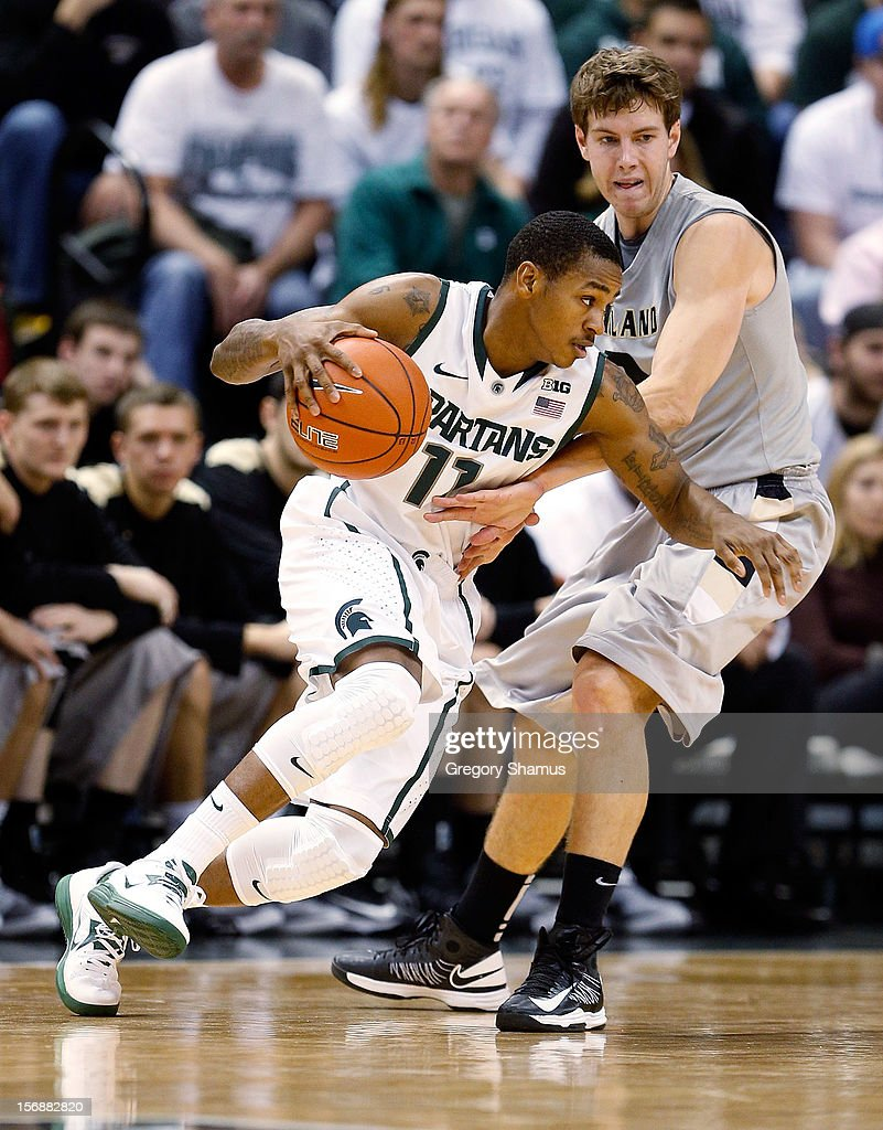 Keith Appling #11 of the Michigan State Spartans drives around Dante Williams #2 of the Oakland Golden Grizzlies at the Jack T. Breslin Students Events Center on November 23, 2012 in East Lansing, Michigan.