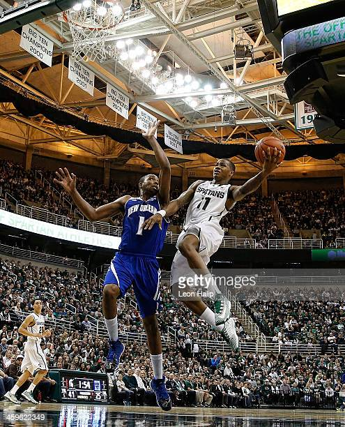 Keith Appling of the Michigan State Spartans drives the ball to the basket during the first half of the game as Tevin Broyles of the New Orleans...