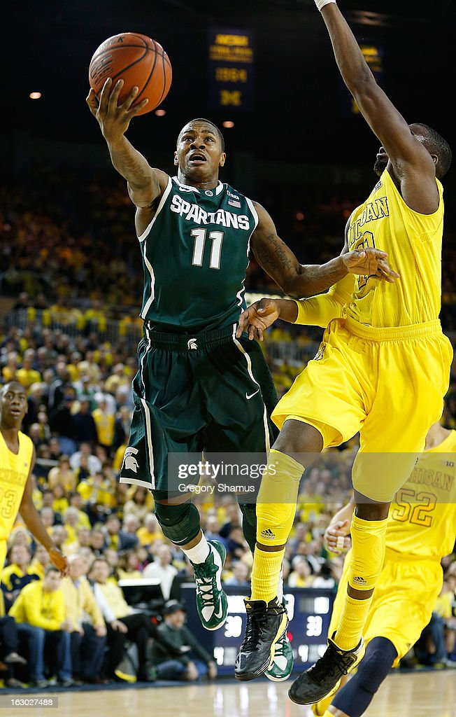 Keith Appling #11 of the Michigan State Spartans gets in for a for a second half basket past Tim Hardaway Jr. #10 of the Michigan Wolverines at Crisler Center on March 3, 2013 in Ann Arbor, Michigan. Michigan won the game 58-57.