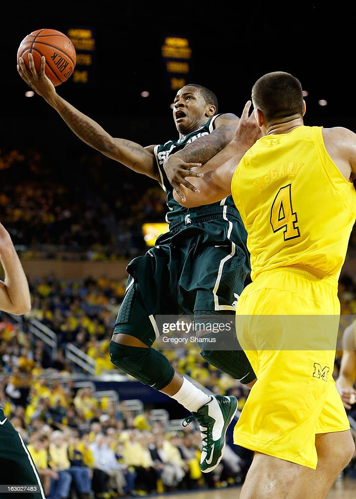 Keith Appling #11 of the Michigan State Spartans tries to get to the basket past Mitch McGary #4 of the Michigan Wolverines of the Michigan Wolverines at Crisler Center on March 3, 2013 in Ann Arbor, Michigan. Michigan won the game 58-57.