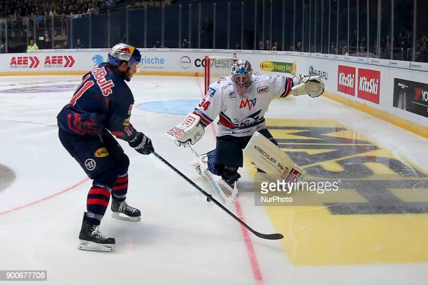 Keith Aucoin of Red Bull Munich vies Chet Pickard of Adler Mannheim during the 38th game day of the German Ice Hockey League between Red Bull Munich...