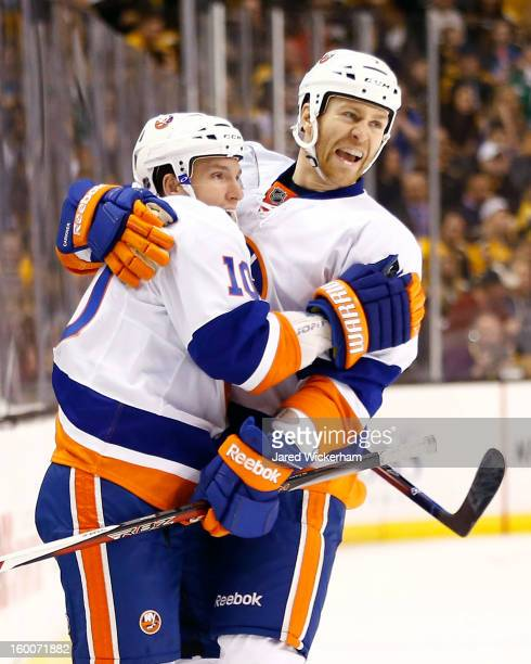 Keith Aucoin of the New York Islanders celebrates with teammate Matt Carkner of the New York Islanders following his goal in the second period during...