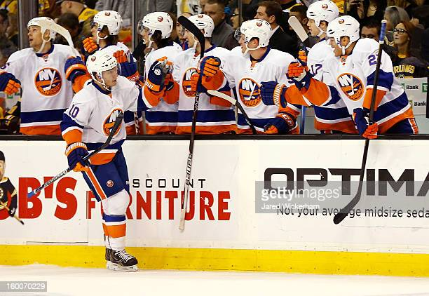 Keith Aucoin of the New York Islanders is congratulated by teammates on the bench after scoring in the first period against the Boston Bruins during...