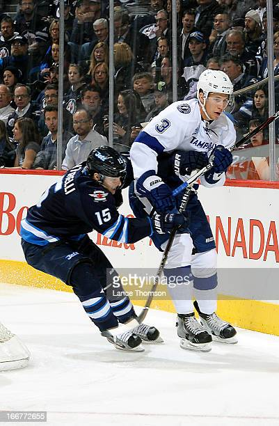Keith Aulie of the Tampa Bay Lightning plays the puck along the boards as Mike Santorelli of the Winnipeg Jets chases from behind during first period...