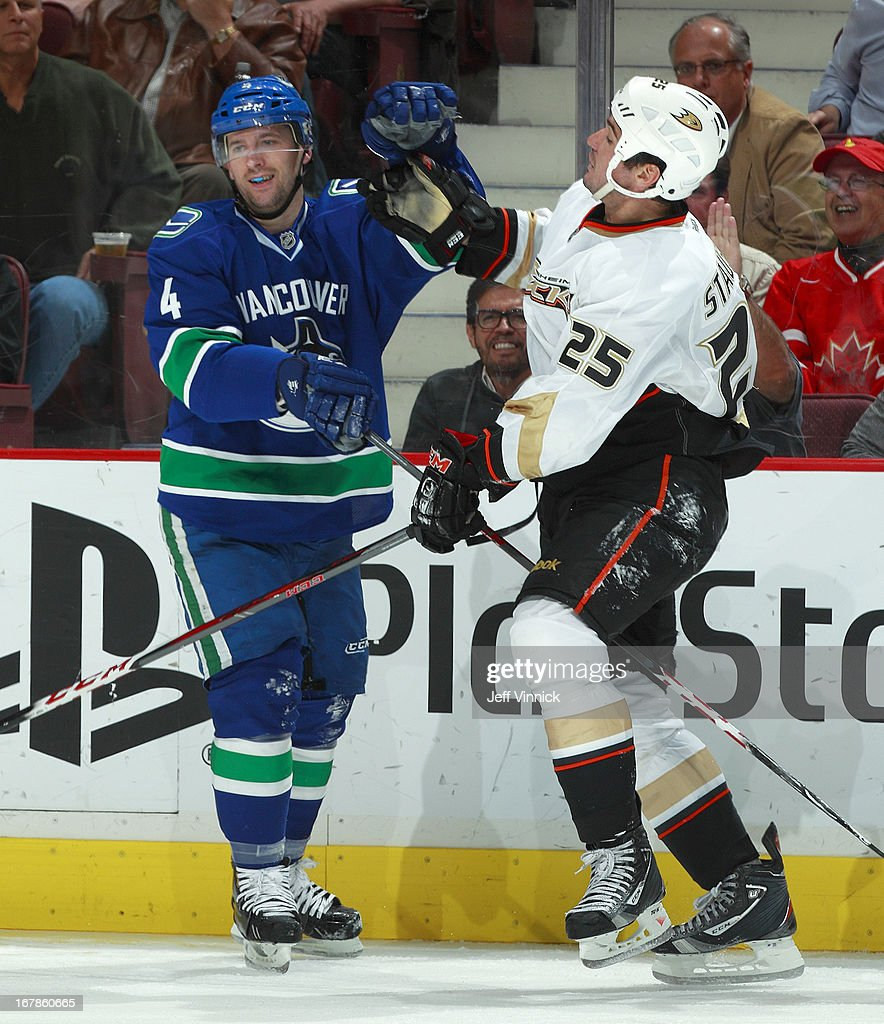 Keith Ballard #4 of the Vancouver Canucks and Brad Staubitz #25 of the Anaheim Ducks exchange words during their NHL game against the Vancouver Canucks at Rogers Arena April 25, 2013 in Vancouver, British Columbia, Canada. Anaheim won 3-1.