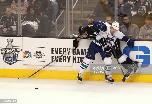 Keith Ballard of the Vancouver Canucks checks Jordan Nolan of the Los Angeles Kings in the third period in Game Four of the Western Conference...