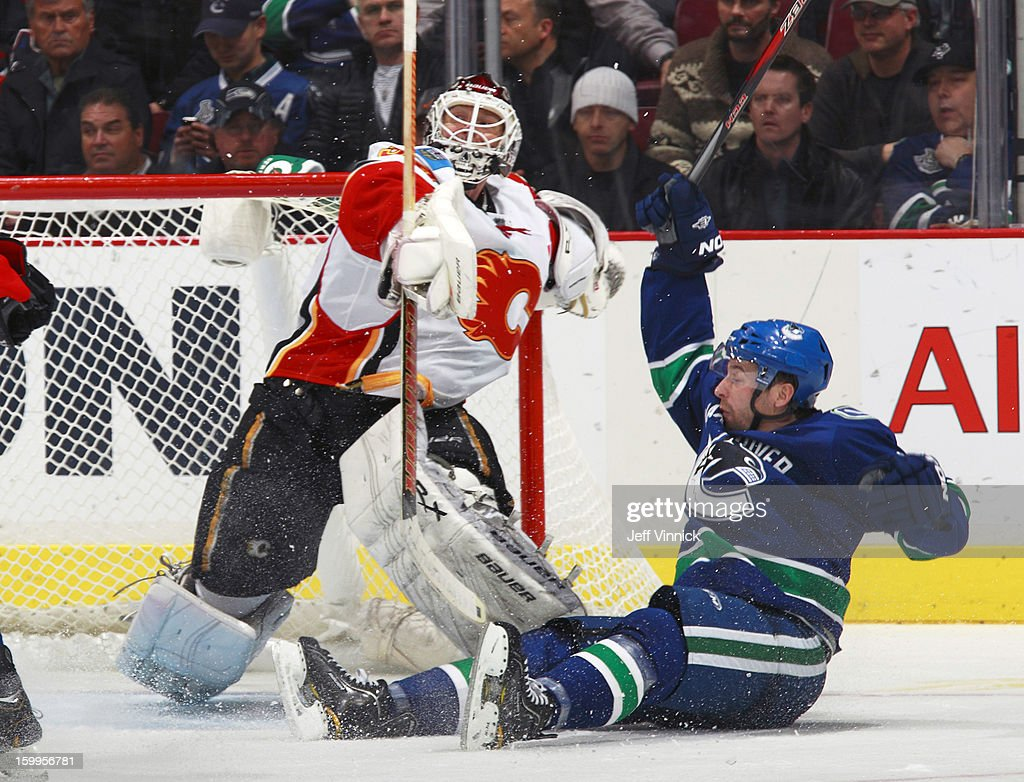 Keith Ballard #4 of the Vancouver Canucks collides with Miikka Kiprusoff #34 of the Calgary Flames during their NHL game at Rogers Arena January 23, 2013 in Vancouver, British Columbia, Canada. Vancouver won 3-2 in a shootout.